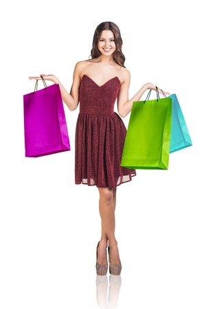 attractive female: Young woman with colorful packages isolated on white. Shopping concept Stock Photo