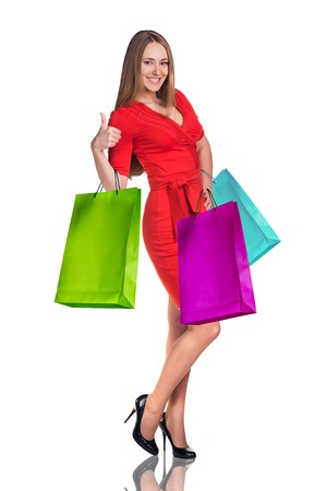 look up: Young woman with colorful packages isolated on white. Shopping concept Stock Photo