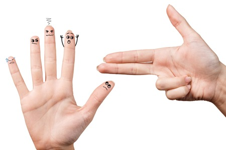 hostages: One gun hand taking hostages another hand with smileys Stock Photo