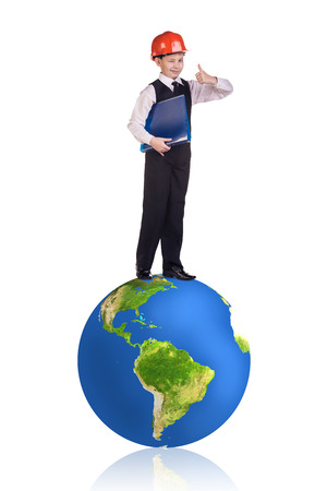 Little cute boy in orange helmet stands on the big earth. Isolated on white.  Stock Photo