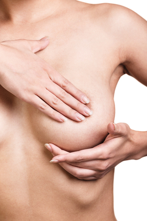 breast nipple: Young woman examining her breasts for signs of breast cancer isolated on white background