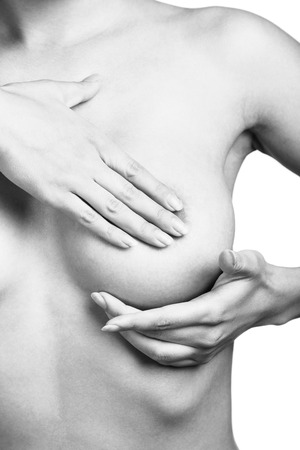 Young woman examining her breasts for signs of breast cancer isolated on white background