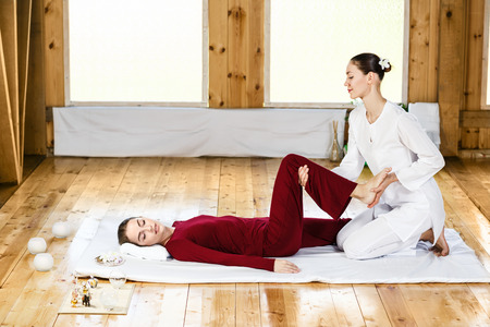 yoga white: Young woman getting traditional thai stretching massage by therapist