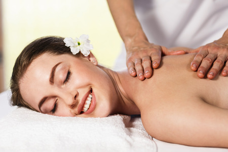 therapy room: Portrait of a beautiful young woman lying on massage at spa center Stock Photo