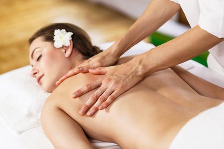 masajes relajacion: Muchacha hermosa joven que yace en mesa de masaje y disfrutar de masajes. Foto de archivo