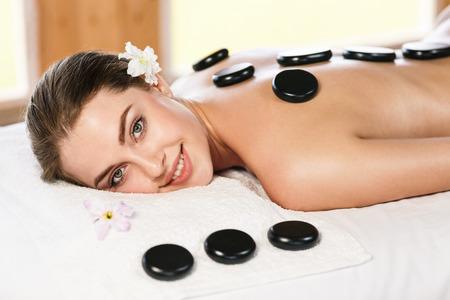masajes relajacion: Mujer hermosa joven que miente en la tabla del masaje y terapeuta de espera