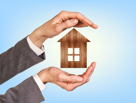 modular home: Wooden house in human hands over blue background Stock Photo