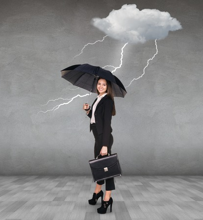 shield: Thunderstorm strikes to businesswoman with umbrella in the gray room Stock Photo