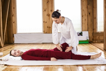 traditional healer: Young woman getting traditional thai stretching massage by therapist