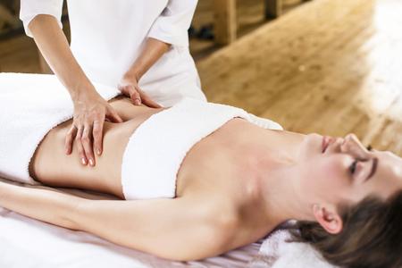 masaje: Hermosa mujer joven que tiene masaje visceral en el centro de spa