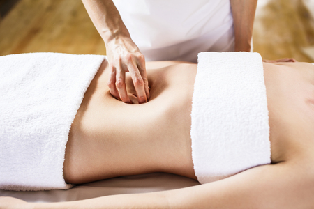 Beautiful young woman having visceral massage. Close-up Stock Photo