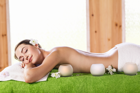 Portrait of a beautiful young woman lying on green towel at spa center