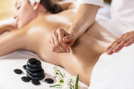 deitado: Mulher bonita nova que aprecia a massagem sobre a mesa no centro de spa