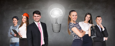 gray bulb: Business people team near big bulb with brain inside on the gray wall background