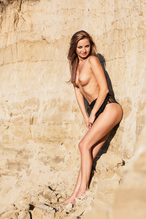 nude nature: Beautiful sexy woman posing on wild rocky coast