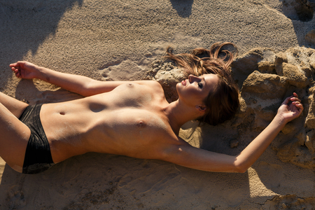 beach breast: Beautiful sexy woman posing on wild rocky coast