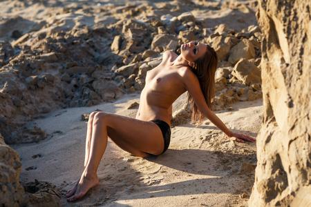 glamour nude: Beautiful sexy woman posing on wild rocky coast