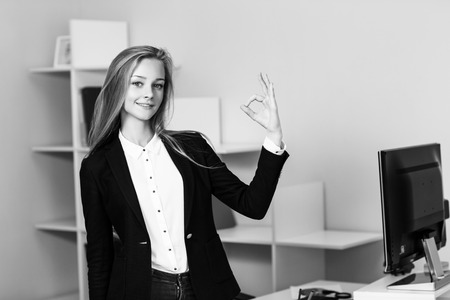 ok hand: Young pretty business woman makes OK sign in blue office