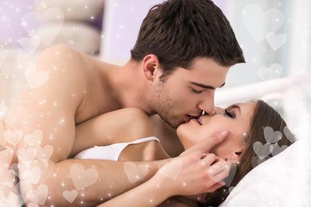amantes en la cama: amantes de la pareja joven tumbado en la cama y besos
