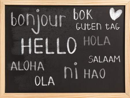 hola: Hello in different languages on chalkboard background Stock Photo
