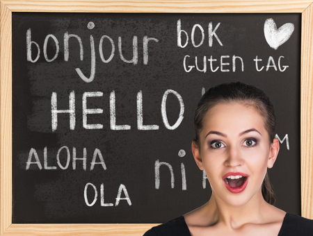 business class travel: Woman near words hello in different languages on chalkboard
