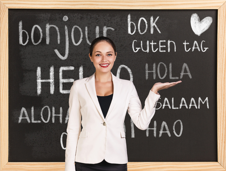 bonjour: Woman near words hello in different languages on chalkboard