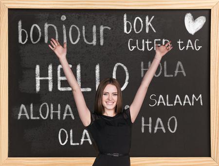 idiomas: Mujer cerca de las palabras de saludo en diferentes idiomas en la pizarra Foto de archivo