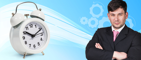 abstract alarm clock: Businessman near classical alarm clock on the blue abstract background