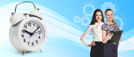 abstract alarm clock: Business women near classical alarm clock on the blue abstract background