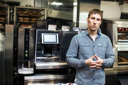 crossed fingers: Young barista standing with crossed fingers with coffee maker on background