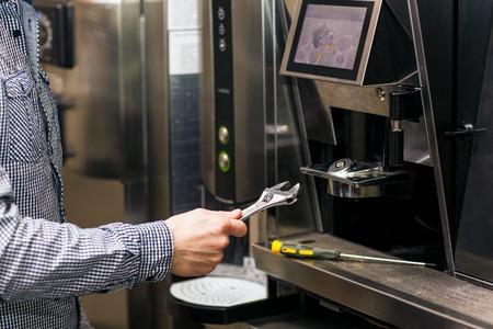 Man geht Kaffeemaschine Maschine mit Schraubenschlüssel zu prerare