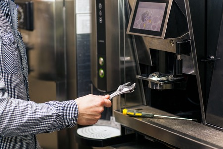 coffee maker machine: Man going to prerare coffee maker machine with wrench
