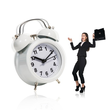 trotters: Business woman stand near big alarm clock isolated on the white
