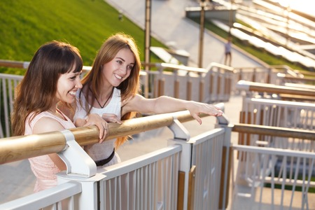 attractive girl: Two cheerful girls stand on the stairs on embarkment