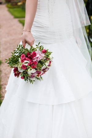 arm bouquet: Bride holds wedding bouquet of different flowers