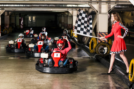 Group of people is driving go-kart car in a playground racing track. Karting concept.