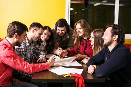 plan de accion: Amigos en discusiones de intercambio de ideas y plan de acción en la mesa Foto de archivo