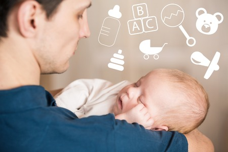beanbag: Happy young father holds sleep new born baby on hands