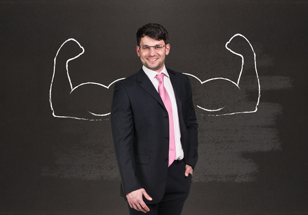 dictatorial: Businessman with drawn powerful hands. Black chalkboard background. Stock Photo
