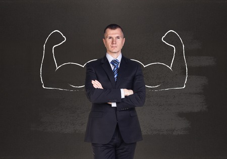 overbearing: Businessman with drawn powerful hands. Black chalkboard background. Stock Photo