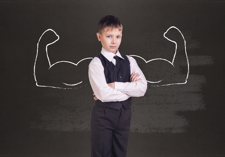 autocratic: Little boy with drawn powerful hands. Black chalkboard background. Stock Photo
