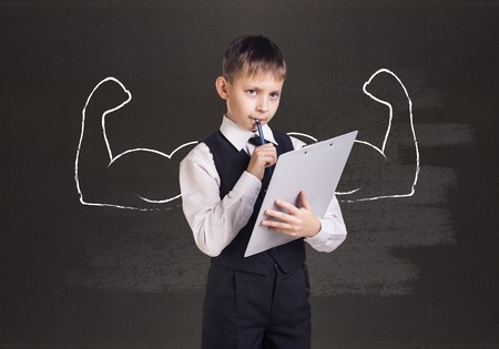 overbearing: Little boy with drawn powerful hands. Black chalkboard background. Stock Photo