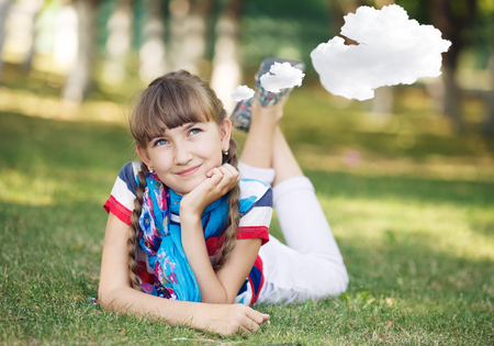 citypark: Little girl resting on meadow and daydreaming