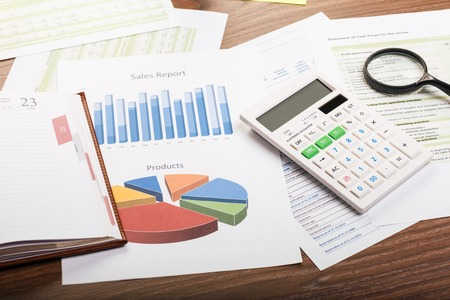 business report: Business concept with magnifying glass, calculator and financial documents Stock Photo