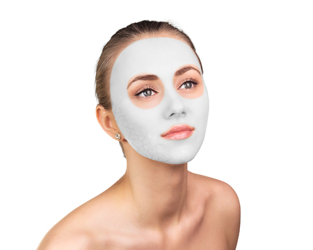 Young woman with clay face mask on her face Imagens