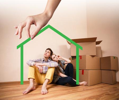 haushaltshilfe: Hand hält grün Hausform mit jungen Familie in