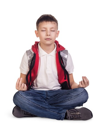 Little cute boy sitting and meditating in lotus position isolated on white 免版税图像