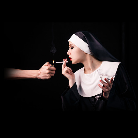 black hands: Hand get a light to smoking young nun with wineglass on the black background.