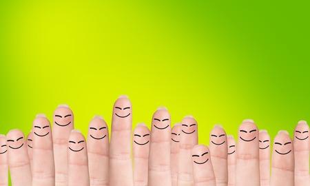 Viele Finger mit gezeichnete Gesichter, steht auf dem grünen Hintergrund