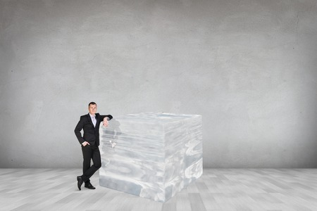 leaned: Businessman near big ice cube in the gray room